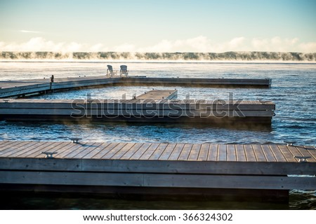 A dock on Georgian Bay at sunrise with Muskoka chairs at the end - stock photo