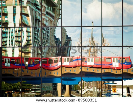 A Docklands Light Railway train reflected on the glass surface of an office block in Canary Wharf. The sails of a tallship docked in West India Quay are also reflected on the right. - stock photo