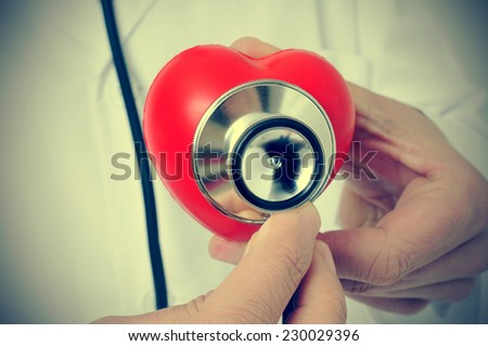 a doctor auscultating a red heart with a stethoscope, with a retro effect - stock photo