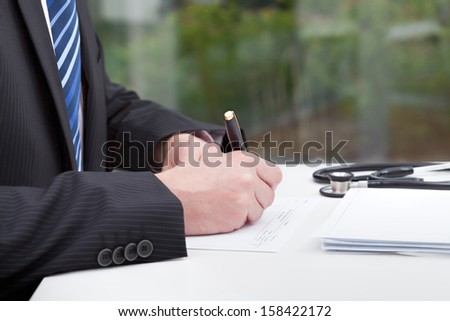 A doctor doing some paperwork in his consulting room