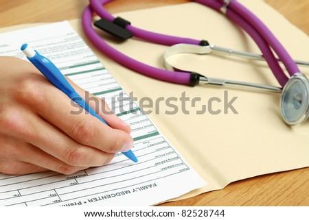 A doctor filling a prescription, close-up shot - stock photo