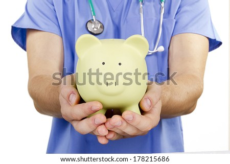 A doctor holding a piggy bank. Payment medicine. - stock photo