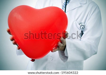 a doctor holding a red heart-shaped balloon, symbolizing the cardiovascular medicine - stock photo