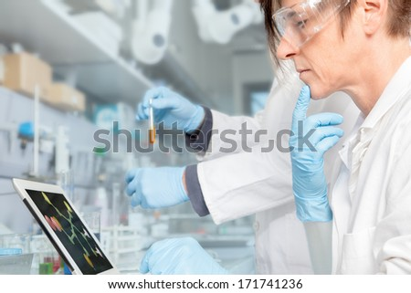 A Doctor is doing some drug research on an electronic device. - stock photo