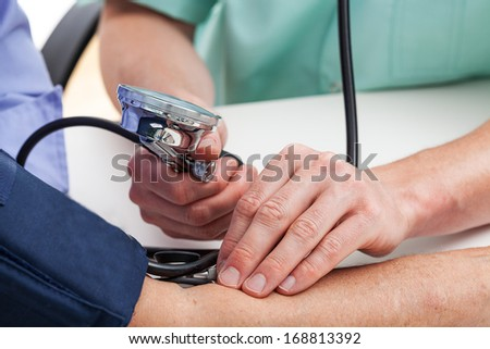A doctor measuring a patient's pressure - stock photo