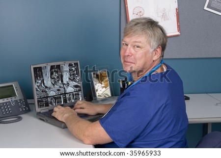 A doctor reviews an MRI on his laptop.  Good for using technology to review imagery as opposed to hard film MRI's. - stock photo