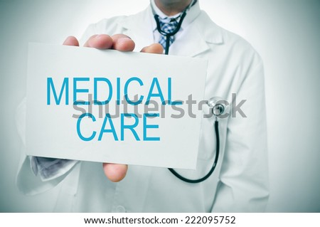 a doctor showing a signboard with the text medical care written in it - stock photo