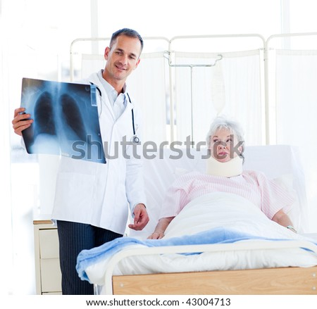 A doctor showing an x-ray to a patient with a neck brace - stock photo