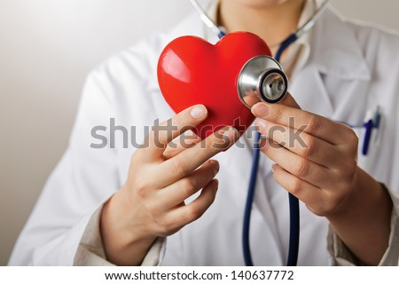 A doctor with stethoscope examining red heart, isolated on white background - stock photo