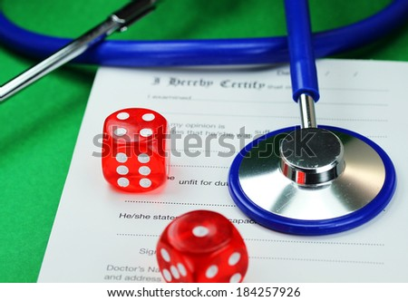 A Doctors desk with two dice placed next to a blue stethoscope all placed on a doctors sick certificate pad, asking the question, do you gamble with your health - stock photo