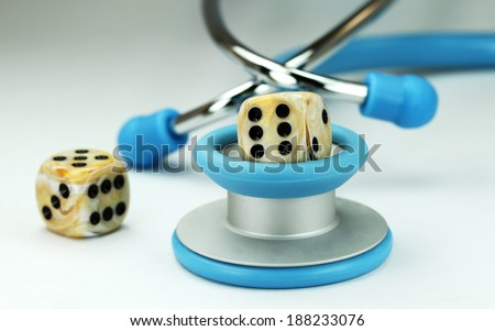 A Doctors light blue stethoscope with two ivory dice with black spots dice placed next to it, asking the question, do you gamble with your health. - stock photo