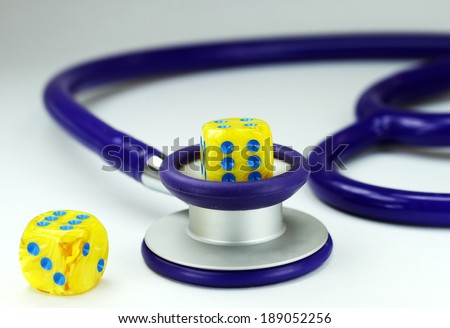 A Doctors purple stethoscope with two ivory marbled dice with black spots placed next to it, asking the question, do you gamble with your health. - stock photo