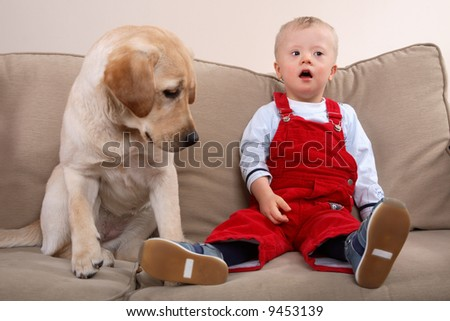A dog and young boy with Down Syndrome together on a sofa.