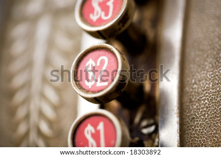A 2 dollar button on a retro dirty cash register - shallow depth of field - stock photo