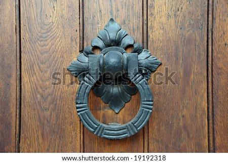 A door knocker on a wooden door. - stock photo