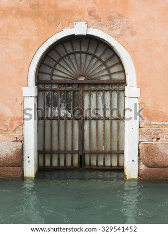 A door on a canal in Venice, Italy as the tide rises. - stock photo