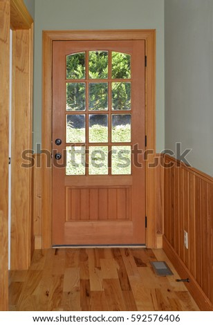 A door with glass panels at the end of a hallway, leading to the yard.