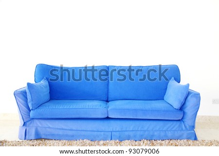 a double blue couch sofa on a blank wall in a living room - stock photo