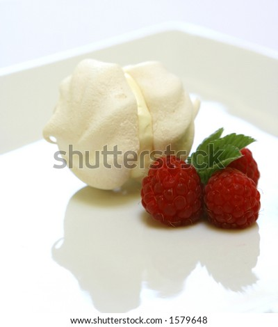 A double cup of meringue filled with cream on a plate with three raspberries as decoration - stock photo
