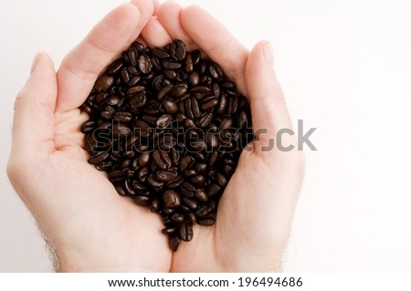 A double handful of dark roasted coffee beans. - stock photo