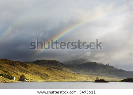 A double rainbow arches over the mountains in the distance. the majestic rock pinnacle of the Old Man of Storr is shrouded in cloud. - stock photo
