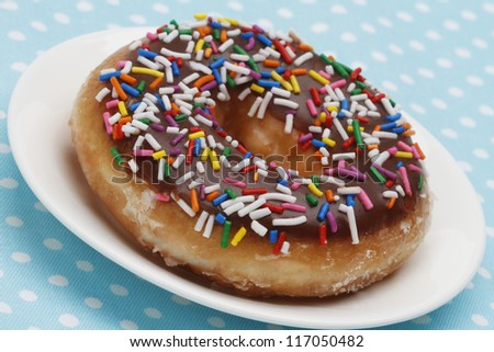 A doughnut with colorful sprinkles - stock photo