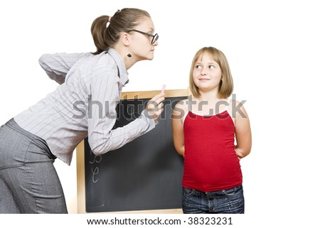A dour female teacher explaining the lesson to a little girlt with severe attitude. - stock photo
