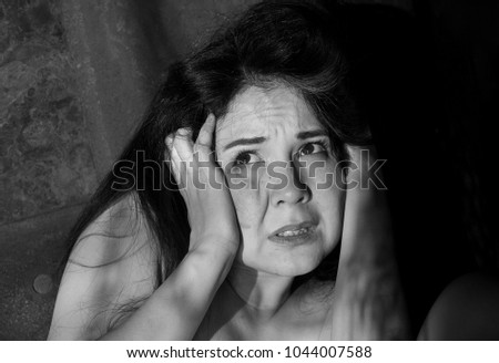 A dramatic and emotional black and white portrait of a young frightened woman with fear