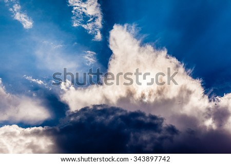 a dramatic cloud formation backlit by the sun - stock photo