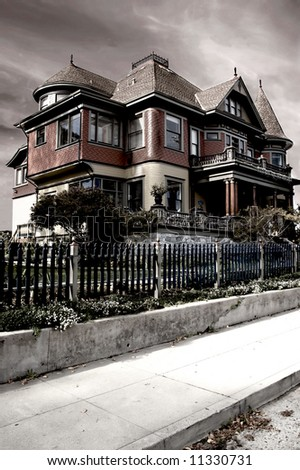 A dramatic image of a Victorian house, processed to give it a foreboding appearance - stock photo