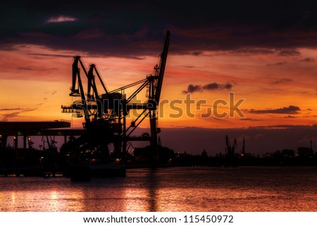 A dramatic sunrise over container terminal - stock photo