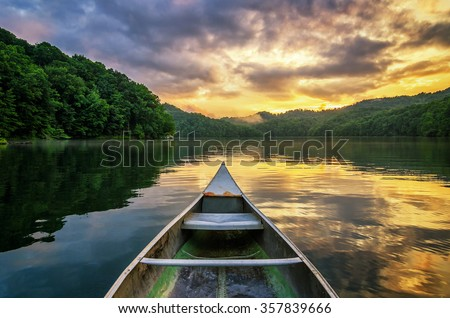 A dramatic sunset from an old canoe on a clam mountain lake in the Appalachian Mountains of Kentucky. - stock photo