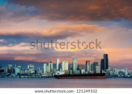 A dramatic sunset paints a beautiful sky over the Seattle, Washington skyline and Elliott Bay with a commercial ship in the foreground. - stock photo