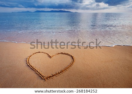 A drawing of a heart on a yellow sand at a beautiful seascape background. - stock photo