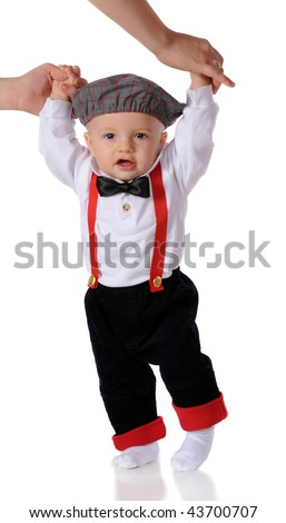 A dressed-up baby boy taking his first steps while holding onto mom's hands.  Isolated on white. - stock photo