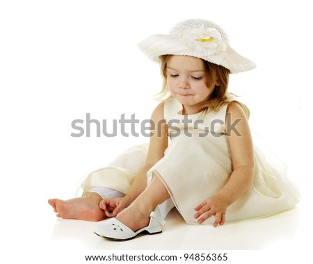 A dressed-up preschooler dressed totally in white putting on her own shoe.  On a white background. - stock photo