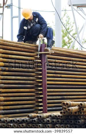 A drilling rig worker. Focus is on the pipes. - stock photo