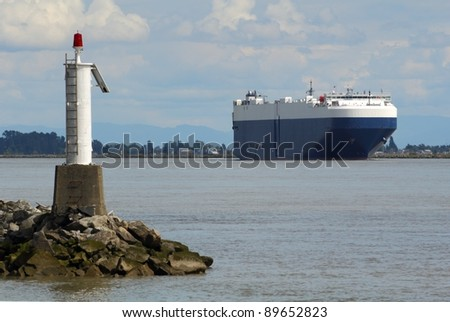 A drive on/drive off car carrier ship ship travels out to sea on the Fraser River in the late afternoon. Near Vancouver, British Columbia, Canada. - stock photo