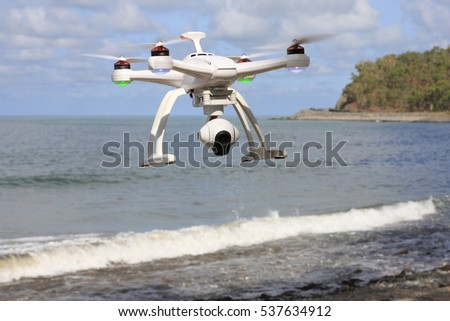 a drone with a camera  flying over the sea