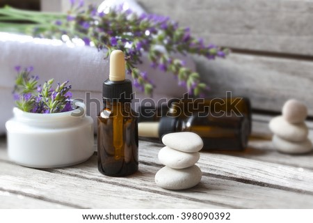 A dropper bottle with lavender essential oil on a old wooden surface. Lavender twig and white towels in the background. - stock photo