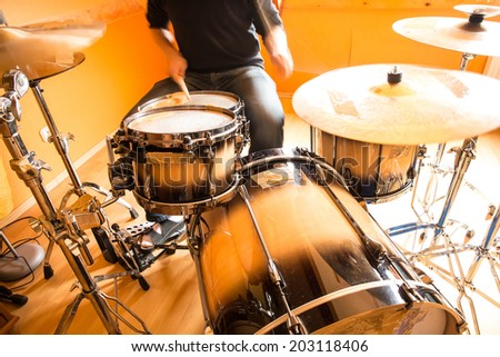 A drummer performing on his Drumset. - stock photo