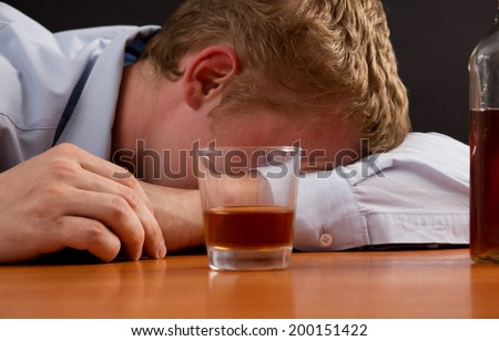 A drunk man is asleep at the table, next to alcohol - stock photo
