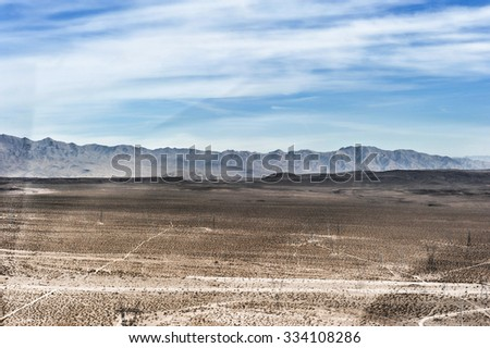 A dry desert view on a sunny day from a helicopter.
