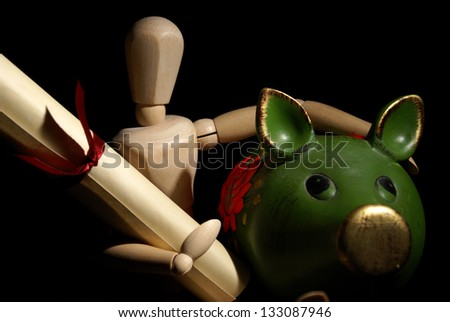A dummy holds a diploma while paying the bank. - stock photo