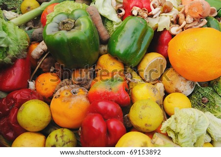 A dumpster full of rotten fruit and vegetables outside a supermarket. - stock photo