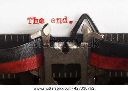 """A dusty typewriter typing """"The End"""". Vintage inscription made by old typewriter with red ink. - stock photo"""