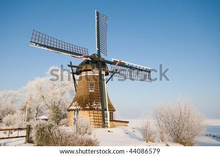A dutch mill in a winter landscape - stock photo