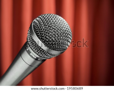 A dynamic microphone over a red background.