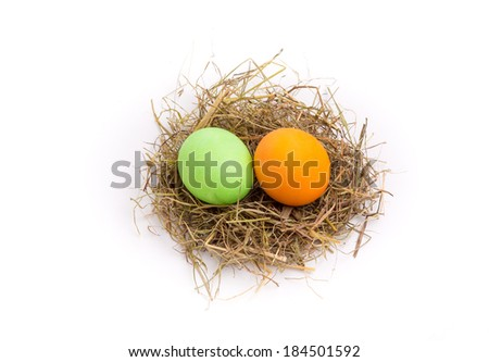A easter straw nest with colored eggs in it.
