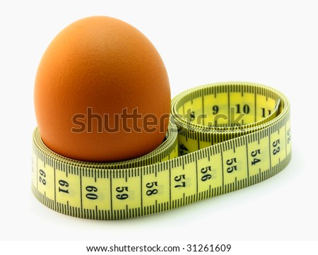 A EGG WITH A MEASURING TAPE AROUND IT. - stock photo